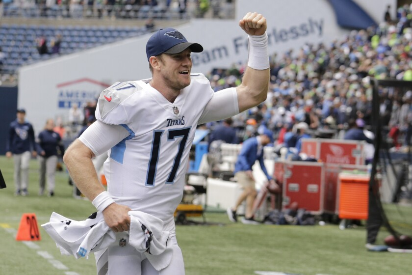 Tennessee Titans quarterback Ryan Tannehill reacts as he runs off the field after his team beat the Seattle Seahawks 33-30 in overtime of an NFL football game, Sunday, Sept. 19, 2021, in Seattle. (AP Photo/John Froschauer)