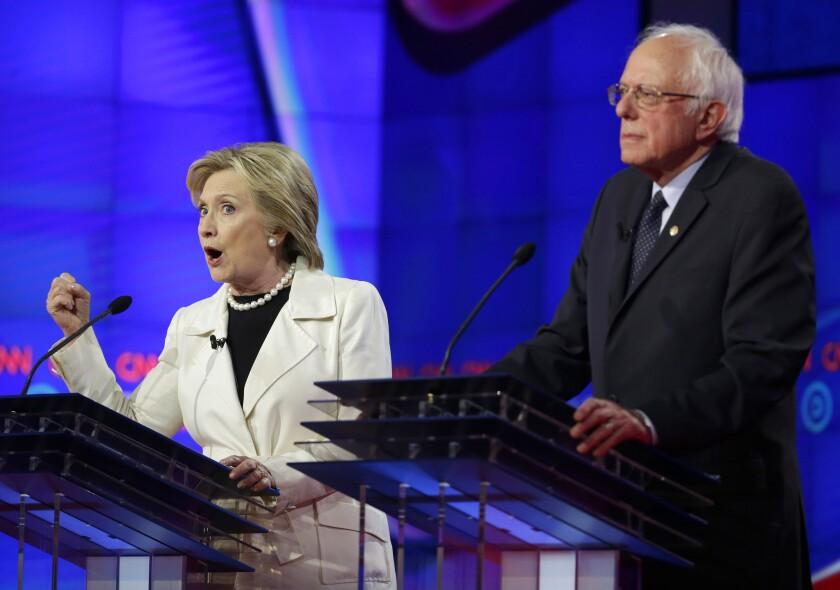 Hillary Clinton speaks while Sen. Bernie Sanders listens during a Democratic presidential debate Thursday night in Brooklyn.
