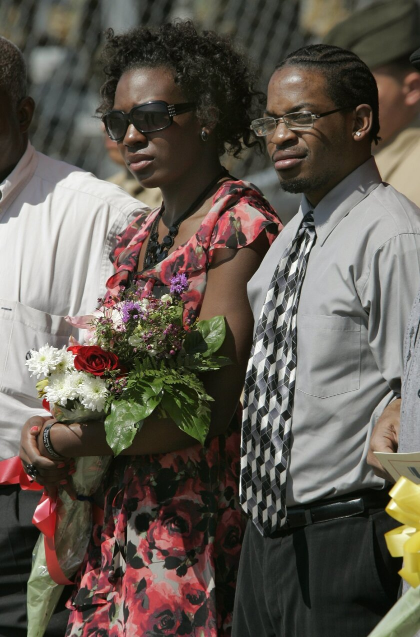 Stacia Harris, the wife of Marine Cpl. Larry D. Harris Jr., holds flowers given to her during the ceremony where her husband, who was killed in action, received the Silver Star Medal for heroism in Afganistan. At right is Kyle Harris, 22,  Larry Harris' brother.