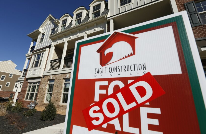FILE - In this Jan. 8, 2015 file photo, a sign with a sold sticker is posted in front of a row of new town homes in Richmond, Va.  Average long-term U.S. mortgage rates rose sharply this week of Nov. 5, 2015,  amid growing expectations that the Federal Reserve may soon raise its key short-term inte