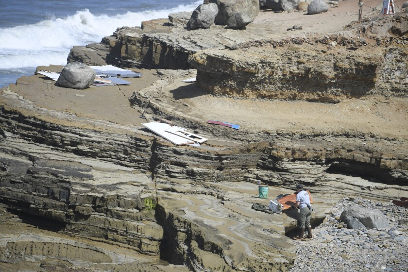 A worker removes wreckage from the tide pools at Cabrillo National Monument after a boat broke apart on the rocks May 2.
