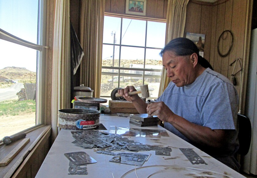 Hopi silversmith Duane Tawahongva makes silver medallions in his home overlooking the desert.