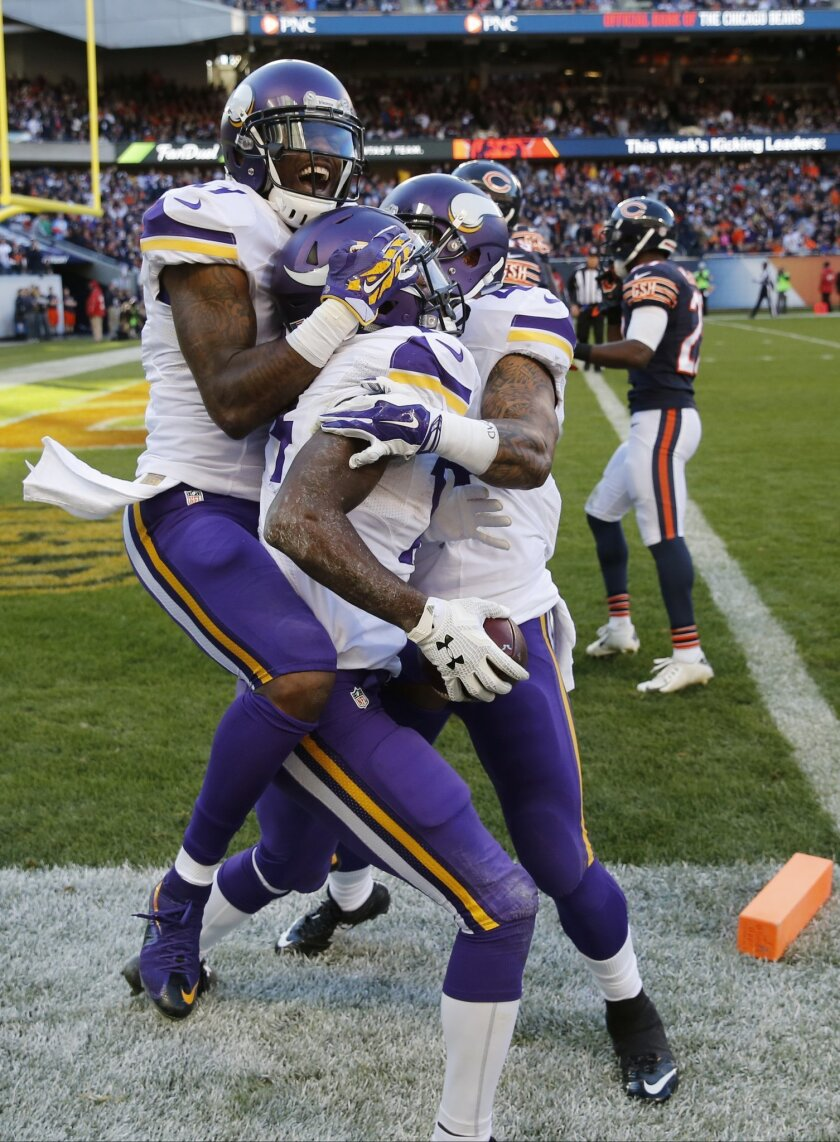Minnesota Vikings wide receiver Stefon Diggs, center, celebrates his touchdown with teammates Mike Wallace, left, and Matt Asiata during the second half of an NFL football game against the Chicago Bears, Sunday, Nov. 1, 2015, in Chicago. The Vikings won won 23-20. (AP Photo/Charles Rex Arbogast)