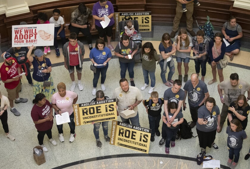 """People with signs stand inside a building. Some signs say """"Abolish abortion: Roe is unconstitutional."""""""