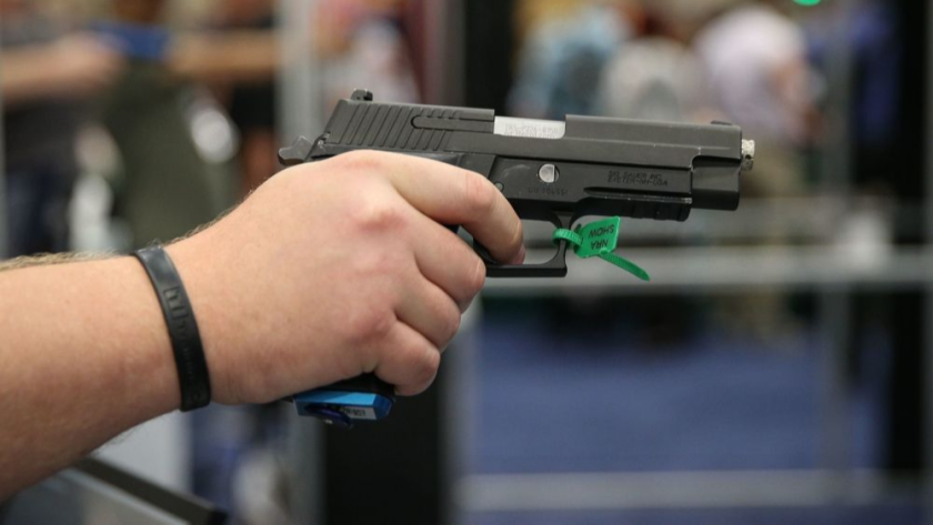 A man aims a firearm in an exhibit hall at the Kay Bailey Hutchison Convention Center during the NRA's annual convention in Dallas in 2018.
