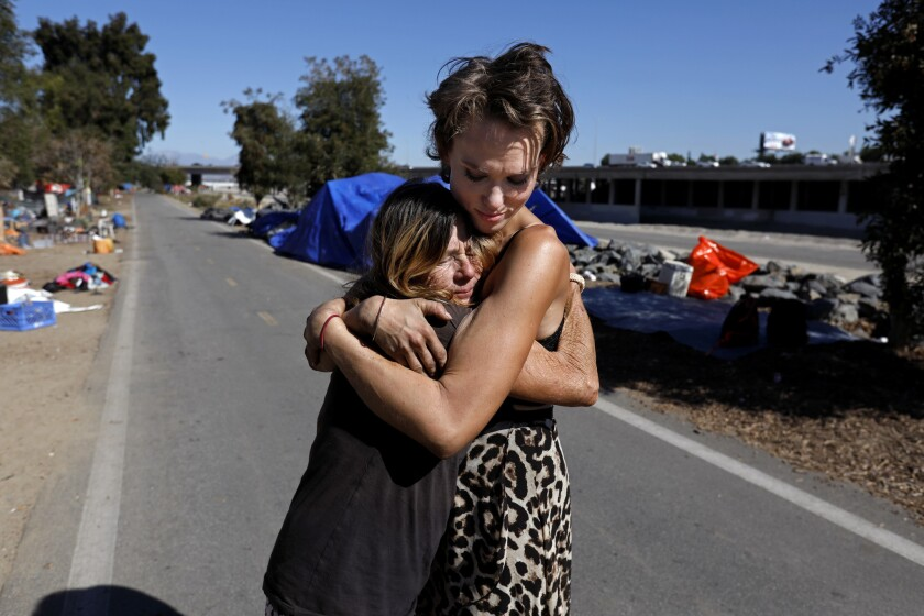 Kathy Schuler, 62, left, who was released from jail Tuesday evening, is given a hug by her granddaughter Ashley Foster, 23, where they live at a homeless encampment along the Santa Ana River in Anaheim.