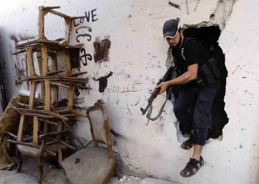 A Sunni gunman in Tripoli, Lebanon, steps through a hole made by fighters to move from street to street during clashes that erupted between supporters and opponents of the Syrian regime. Lebanese officials said a cease-fire had gone into effect there.