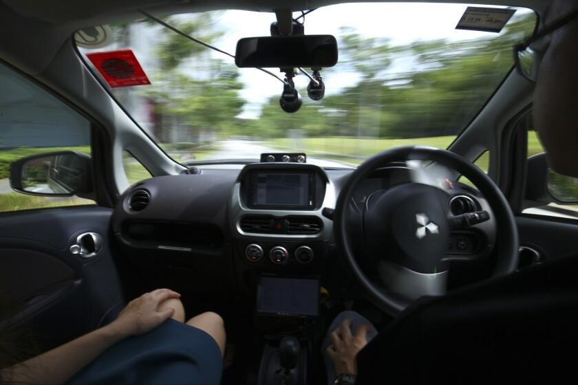 Un conductor, derecha, retira las manos del volante de un auto autónomo durante una prueba de manejo en Singapur, el miércoles 24 de agosto del 2016. Los primeros taxis autónomos del mundo, operados por nuTonomy, empresa de software para vehiculos autónomos, recogerán pasajeros en Singapur a partir del jueves 25 de agosto. (AP Foto / Yong Teck Lim)