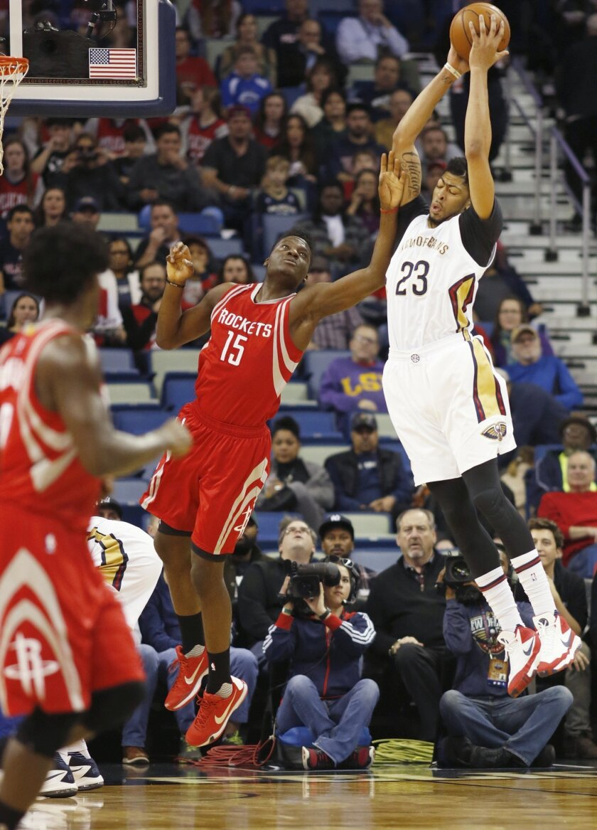 New Orleans Pelicans forward Anthony Davis (23) captures a rebound against Houston Rockets forward Clint Capela in the first half of an NBA basketball game in New Orleans, Monday, Jan. 25, 2016. (AP Photo/Max Becherer)