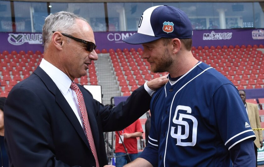 Padres manager Andy Green meets with baseball commissioner Rob Manfred before Saturday's game in Mexico City against the Astros.