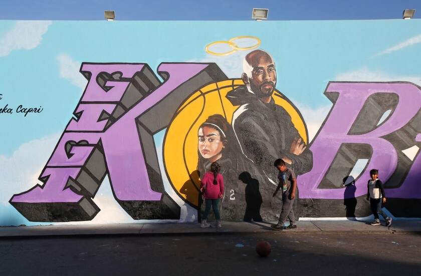 Children gather late last month in front of a newly painted mural honoring Kobe and Gianna Bryant on the side of El Toro Bravo market in Costa Mesa. Days earlier, the Bryants were killed along with seven other people in a helicopter crash in Calabasas.