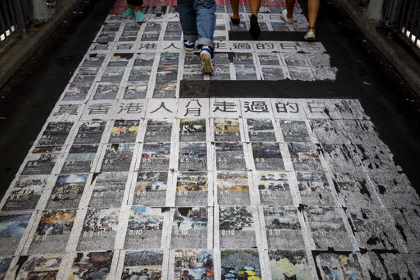 """People walk photos showing the recent protests with words """"The days the Hong Kong people have passed"""" at a pedestrian overhead bridge in Hong Kong, Wednesday, Sept. 25, 2019. Hong Kong leader Carrie Lam said Tuesday, Sept. 24 she doesn't expect a town hall meeting this week to find answers to the months-long pro-democracy protests but hopes it will be a step forward in the """"long journey"""" to reconciliation. (AP Photo/Vincent Thian)"""
