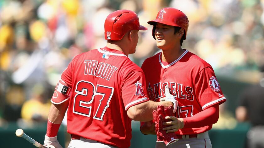 Shohei Ohtani of the Angels is congratulated by Mike Trout after getting his first major league hit on opening day last season..
