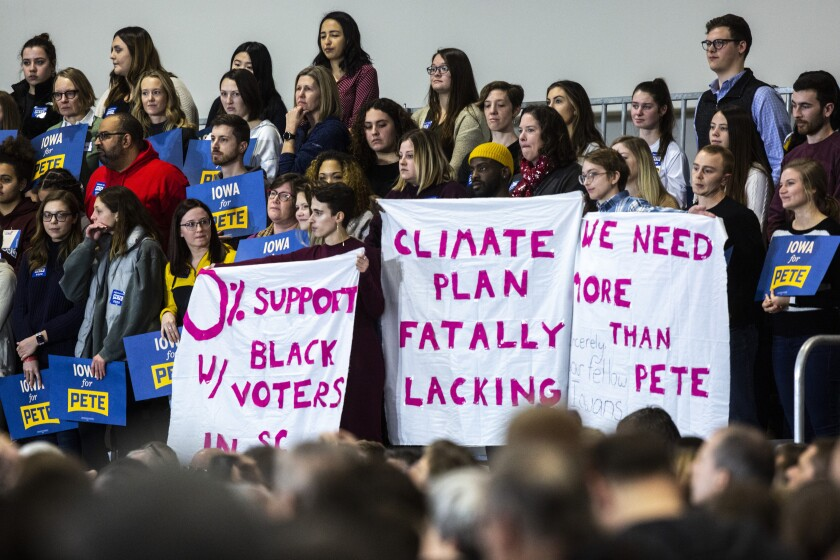 Protesters hold up signs as Democratic presidential candidate Pete Buttigieg, mayor of South Bend, Ind., starts to speak during a town hall in Coralville, Iowa.