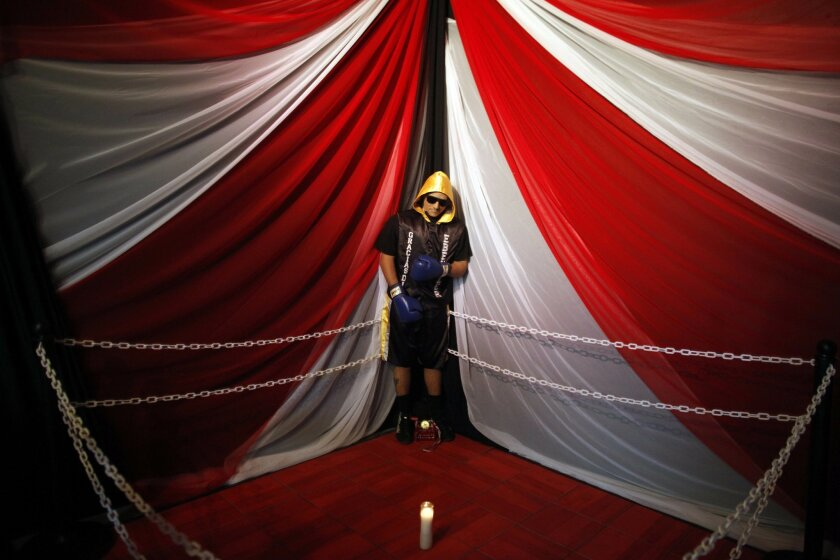 The body of boxer Christopher Rivera, who was shot to death on Sunday, is propped up in a fake boxing ring during his wake at the community recreation center within the public housing project where he lived in San Juan, Puerto Rico, Friday, Jan. 31, 2014.  Elsie Rodriguez, vice president of the Mar
