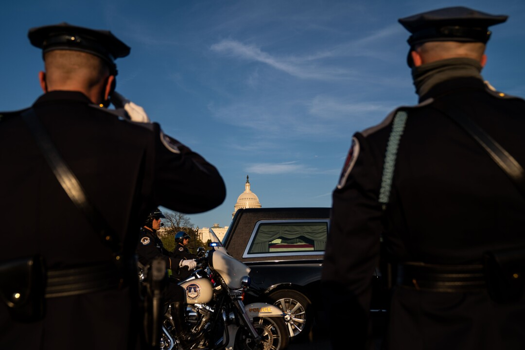 """Officers salute a procession hearse carrying Capitol Police Officer William """"Billy"""" Evans."""