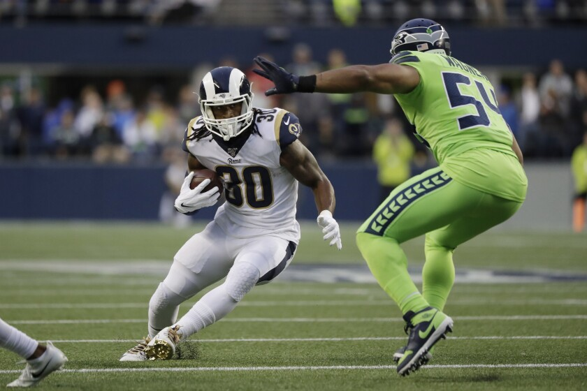 The Rams' Todd Gurley tries to evade Seahawks middle linebacker Bobby Wagner.