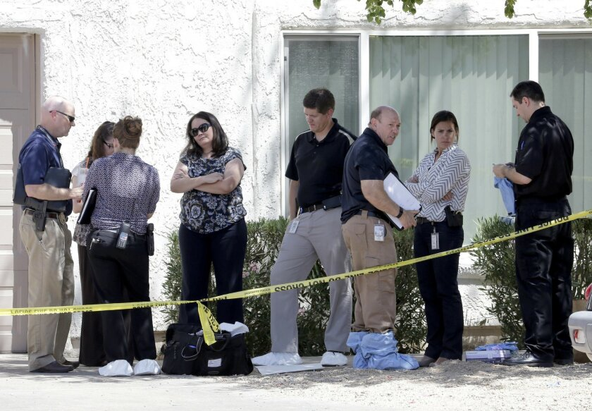 Law enforcement officials stand outside a home, Thursday, June 2, 2016 in Phoenix where three boys were killed during a several hour period Wednesday night.  The boy's mother was hospitalized in critical condition with self-inflicted stab wounds according to Phoenix police. (AP Photo/Matt York)