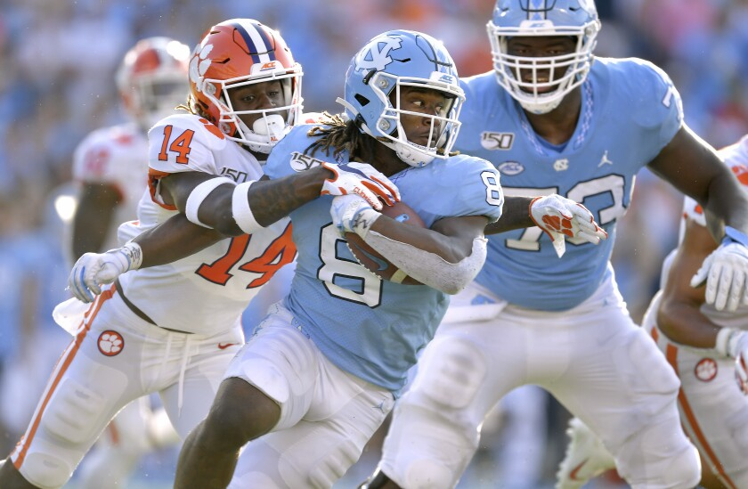 Clemson's Denzel Johnson (14) tackles North Carolina's Michael Carter (8) during the second half on Saturday in Chapel Hill, N.C. Clemson won 21-20.