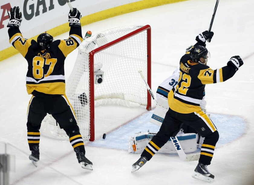 Pittsburgh Penguins' Sidney Crosby (87) and Patric Hornqvist, right, celebrate a goal by Conor Sheary against San Jose Sharks goalie Martin Jones (31) during overtime in Game 2 of the NHL hockey Stanley Cup Finals on Wednesday, June 1, 2016, in Pittsburgh. The Penguins won 2-1 to take a 2-0 lead in