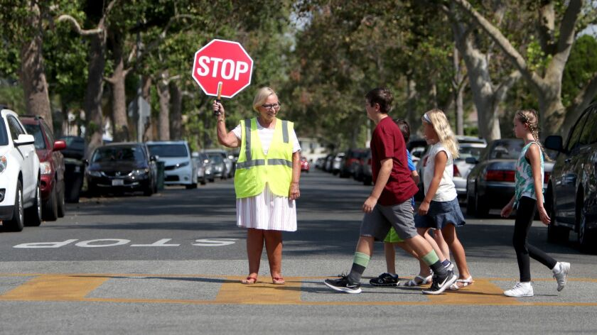 Community volunteer Linda Walmsley shows children how to properly cross the street with the aid of a