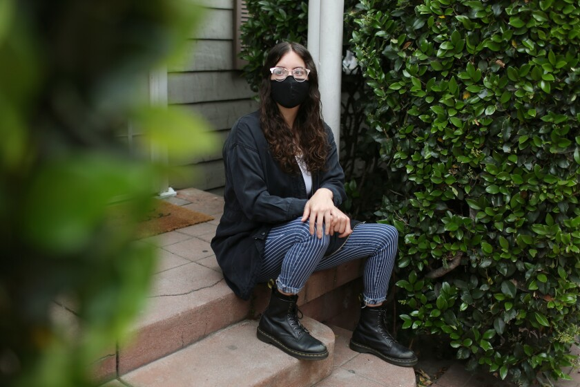 Shelby Bernstein sits outside with a mask on