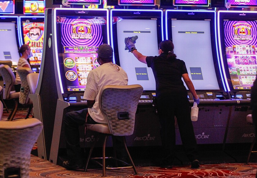 An environmental services worker sanitizes a slot machine on opening day at Sycuan Casino on May 20, 2020 in El Cajon, California.