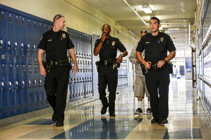Los Angeles school police officer Henry Anderson, second from left, with Gardena police officers at Robert E. Peary Middle School in Gardena.
