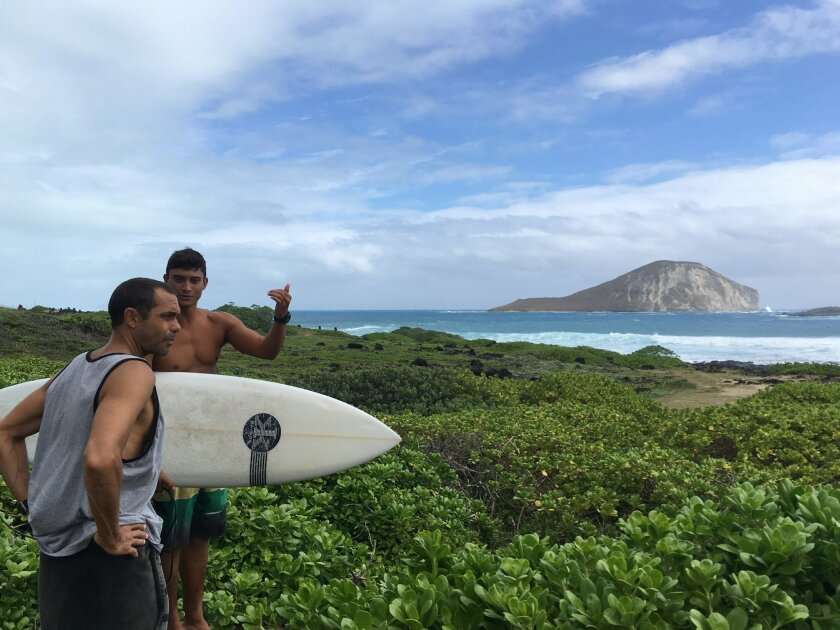 Hopena Pokipala carries a surfboard while discussing wave conditions with Kaipo Guerreo at Makapuu Beach in Waimanalo, Hawaii on Saturday, Sept. 3, 2016. A hurricane watch is canceled for Hawaii as Hurricane Lester tracks north of the state. But the hurricane is generating large waves. (AP Photo/Je