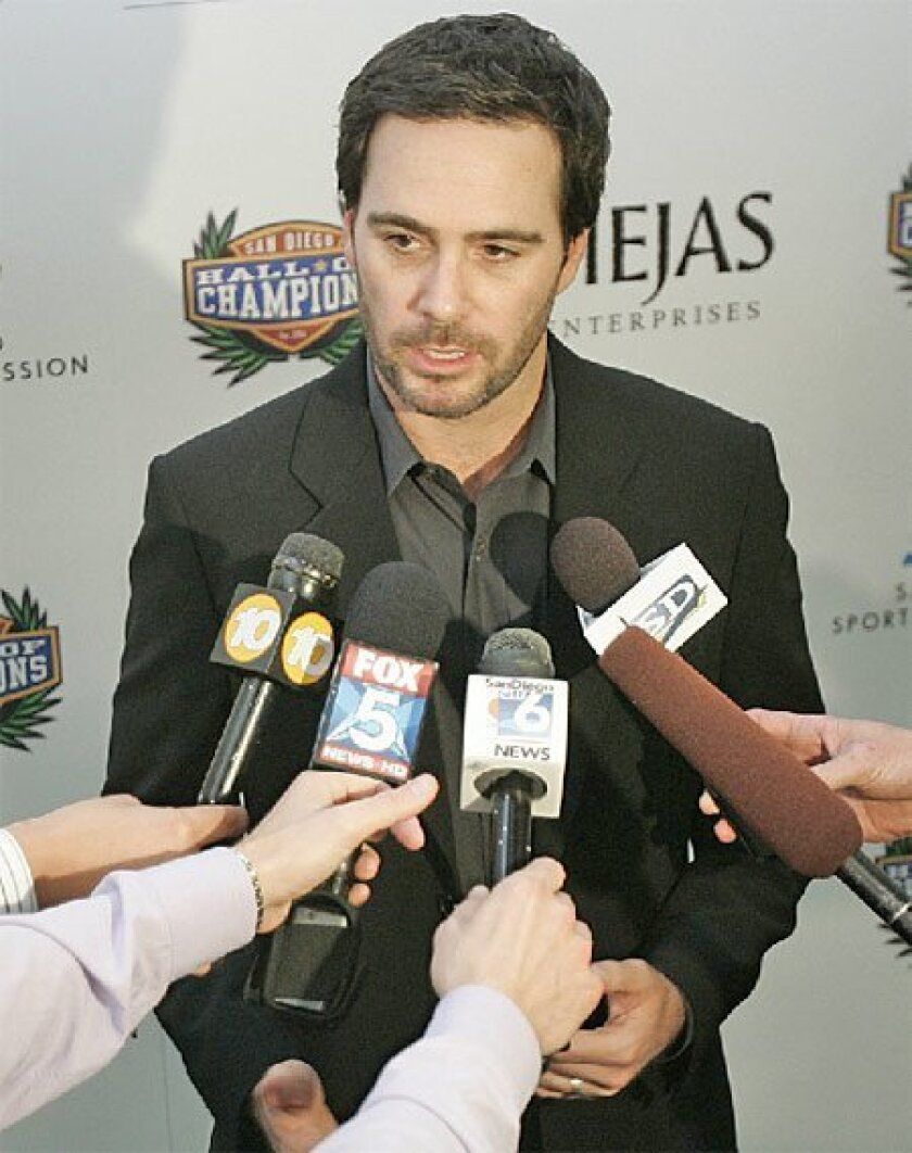 Jimmie Johnson, hoping to become the first in NASCAR history to win four straight titles,  talks with reporters during the Hall of Fame ceremony. (Sean M. Haffey / Union-Tribune)
