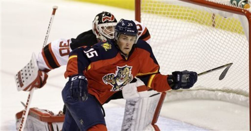 New Jersey Devils goalie Martin Broderu (30) and Florida Panthers' Drew Shore (15) look for the puck after a shot on goal during the second period of a NHL hockey game in Sunrise, Fla., Saturday, March 30, 2013. (AP Photo/J Pat Carter)