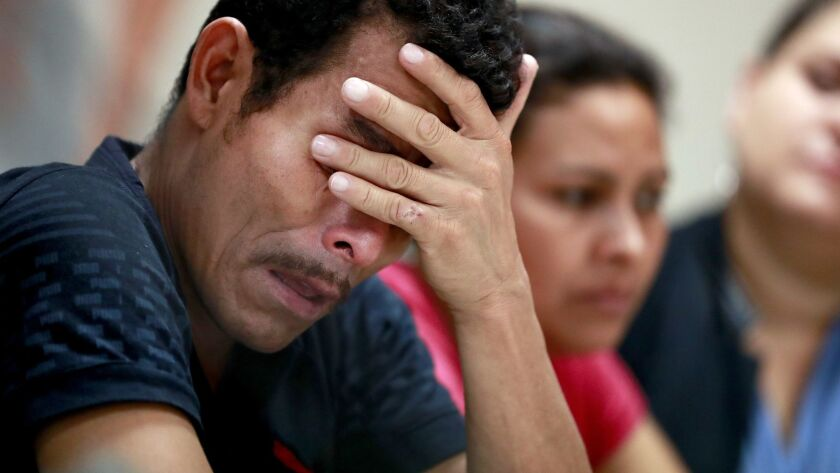 Melvin, foreground, and Iris, both from Honduras, listen as they hear other immigrants tell of their separation from their children during a news conference Monday in El Paso, Texas.