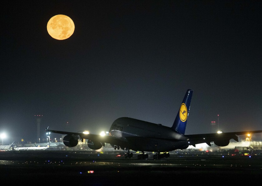 A Lufthansa A380 aircraft lands as the full moon shines at the international airport in Frankfurt, Germany, Sunday, Oct. 13, 2019. (AP Photo/Michael Probst)