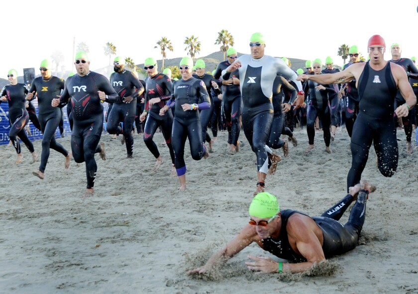 Swimmers make their way down the beach during the start of the Nautica Malibu Triathlon at Zuma beach in Malibu, Calif.