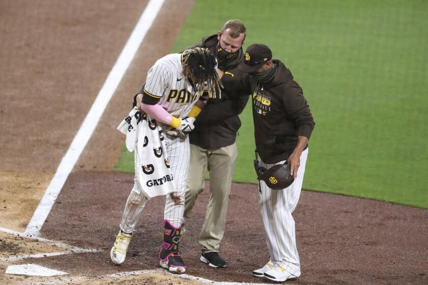 El gerente de los Padres de San Diego, Jayce Tingler y un entrenador ayudan a Fernando Tatis Jr