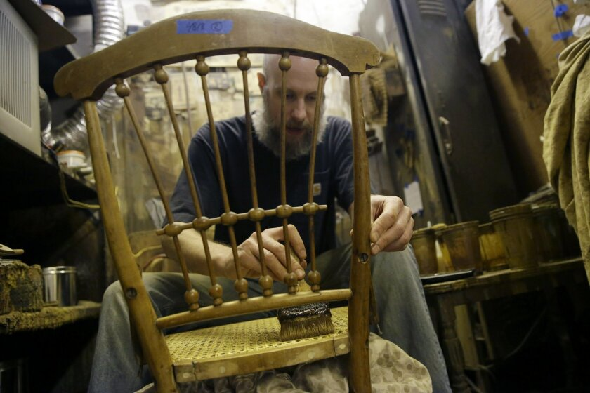 In this Thursday, Nov. 5, 2015, photo, Sean Bausert stains a chair at the Veterans Caning & Repair shop in New York. In a dusty, cluttered shop that seems oddly out of place in modern New York, a group of artisans is among the last still practicing a dying trade: chair caning. The painstaking art o