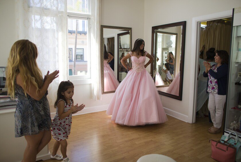 Natalie Anaya, 14, of Santa Ana gets cheers from her mom Ana Perez, sister Isabella Perez, 5, and shop owner Lilia Cerpas, right, while trying on a pink quinceañera dress at Genesis Bridal Boutique in Santa Ana.
