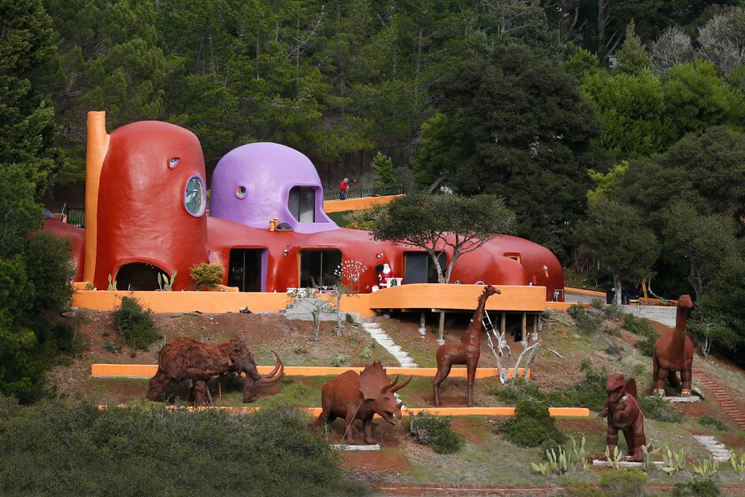 """A menagerie stands guard at the """"Flintstone House"""" in Hillsborough, Calif. Three dinosaurs, a giraffe and mastodon appeared recently near the home that sold in 2017 for $2.8 million."""