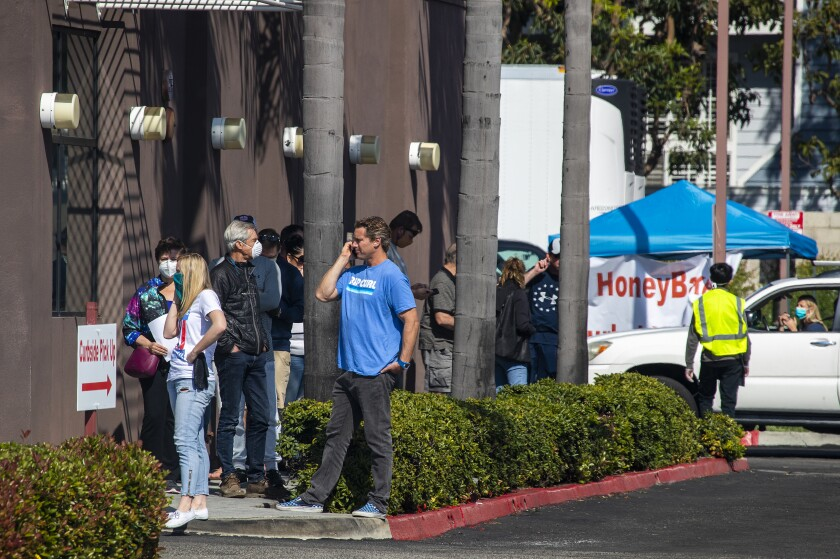 Patrons wait to pick up Easter ham at HoneyBaked Ham in Huntington Beach.