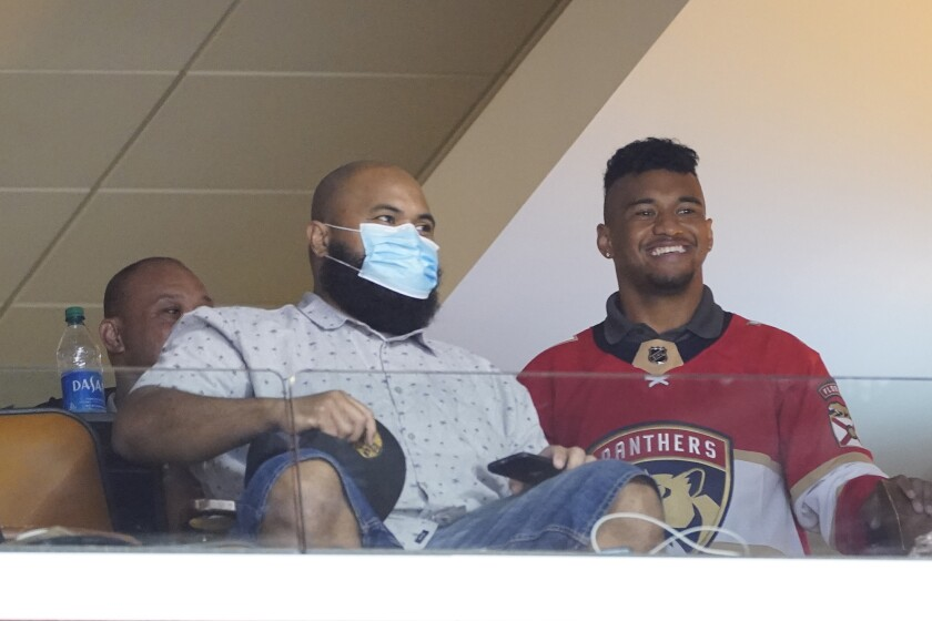 Miami Dolphins quarterback Tua Tagovailoa, right, watches the first period of an NHL hockey game between the Florida Panthers and the Carolina Hurricanes, Monday, March 1, 2021, in Sunrise, Fla. (AP Photo/Wilfredo Lee)
