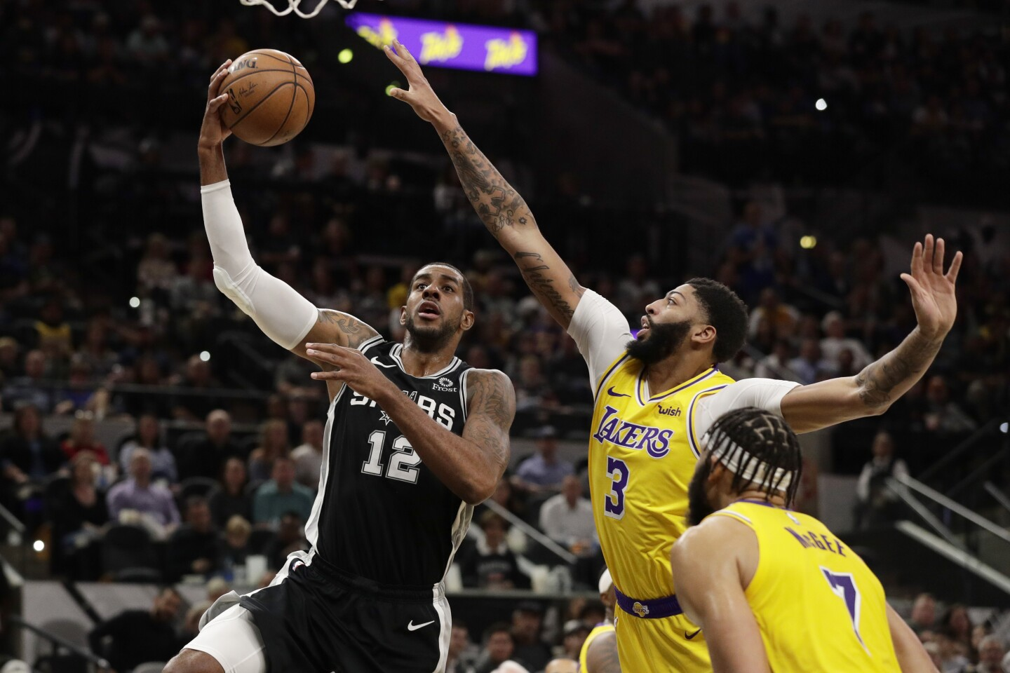 San Antonio Spurs center LaMarcus Aldridge (12) shoots past Los Angeles Lakers forward Anthony Davis (3) during the first half of an NBA basketball game, in San Antonio, Monday, Nov. 25, 2019. (AP Photo/Eric Gay)