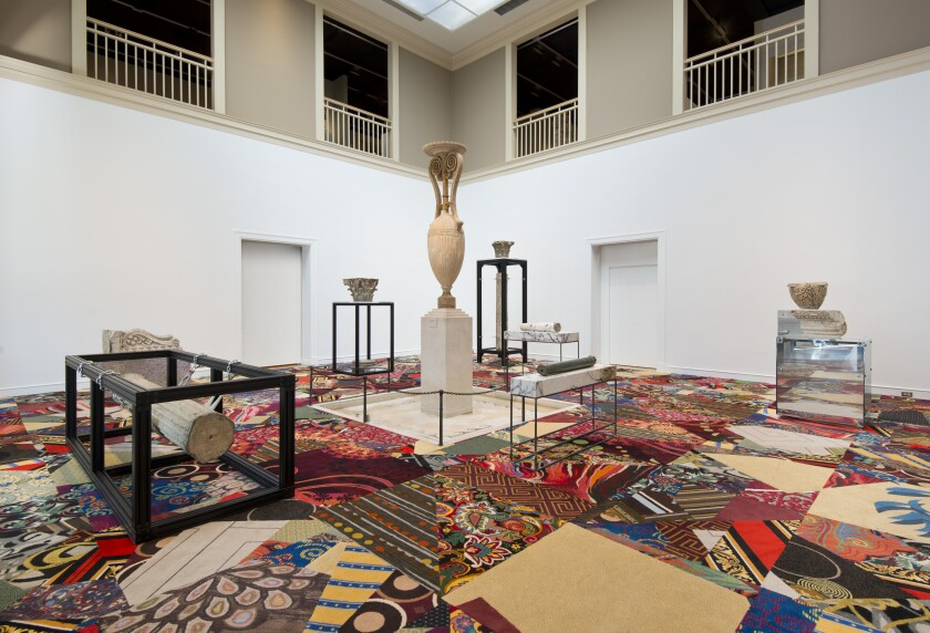 A horizontal image shows a quilt of garish casino carpets topped by architectural fragments from ancient ruins.