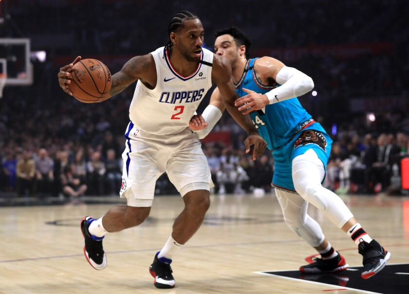 Clippers' Kawhi Leonard (2) dribbles into the defense of Memphis Grizzlies' Dillon Brooks (24) during the first half at Staples Center on Monday.