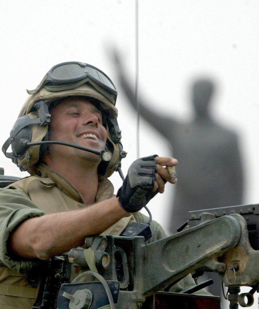 FILE - In this April 9, 2003 file photo, Staff Sgt. Nick Popaditch of the 3rd Battalion, 4th Marines Regiment, smokes a cigar while standing on top of his tank, as he arrives at a main crossroad in downtown Baghdad. A statue of then Iraqi President Saddam Hussein is in the background. On April 7, 2