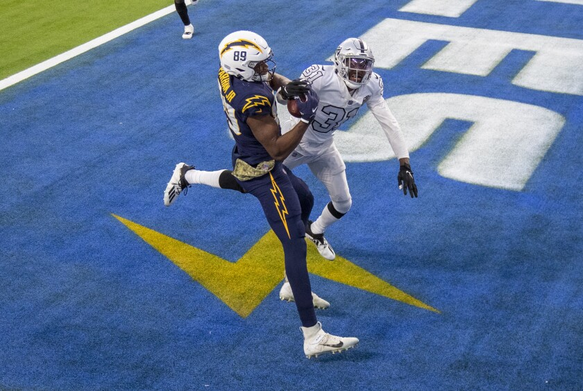 The Chargers' Donald Parham appears to make the winning catch against the Raiders' Isaiah Johnson, but he couldn't hang on.