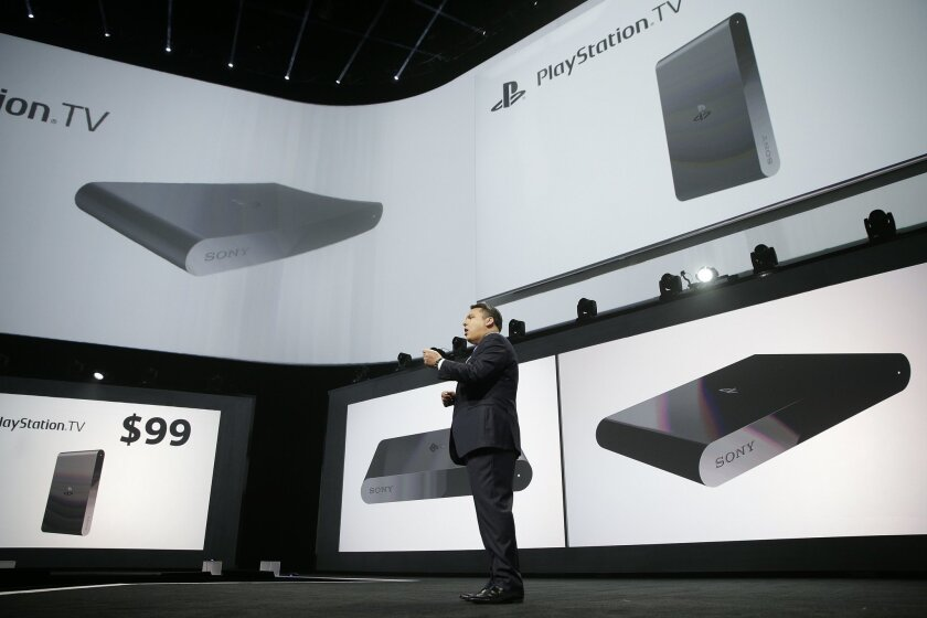 Shawn Layden, president and CEO of Sony Computer Entertainment America, introduces the PlayStation TV during a presentation at the Electronic Entertainment Expo on Monday, June 9, 2014, in Los Angeles. The $99 device will let users stream video, older PlayStation titles and games for Sony's handheld PlayStation Vita system to any TV. (AP Photo/Jae C. Hong)