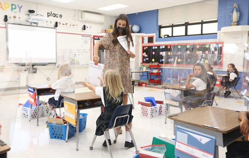 Teacher Megan Hayes hands out assignments in her classroom.