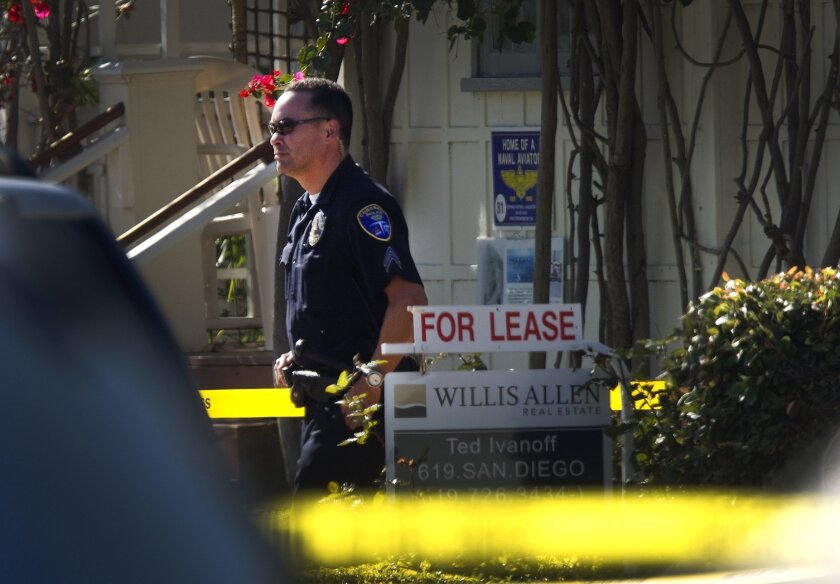 A Coronado police sergeant stands near the condominium on Park Place where four people were found dead at about 2:30 a. m. Sunday morning. It is not known the circumstances of the deaths, however, the Naval Criminal Investigative Service were at the crime scene, as is the procedure when Navy or Mar