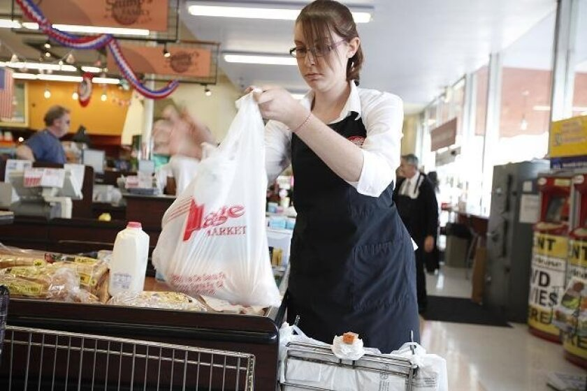 Kalene Lozick, a bagger at Stump's Family Marketplace in Point Loma loads groceries into a plastic bag on June 2, 2010.