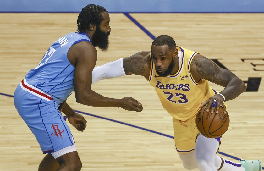 Lakers forward LeBron James drives with the ball against Houston Rockets guard James Harden.